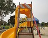 A roadblock sign chained to a slide at a playgr...