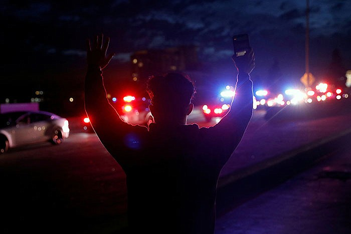 A demonstrator raises his arms towards a convoy of police vehicles during a p...