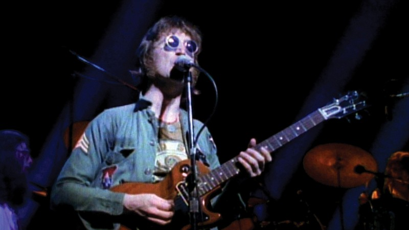 John Lennon is featured in archival footage and interviews talking about