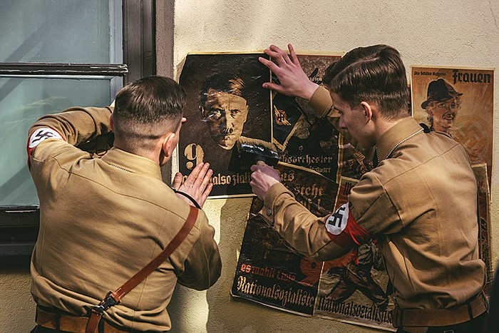 Drama reconstruction: Stormtroopers in uniforms post Hitler posters on wall.
