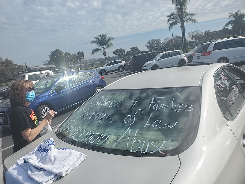 A woman decorates her car in the San Diego Zoo parking lot before a car carav...