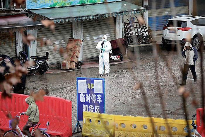 In January 2020, a worker in a protective suit is seen at the Huanan Seafood ...