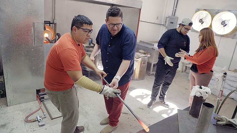 Host Jorge Meraz gets a lesson on glass blowing at Holdman Studios South in E...