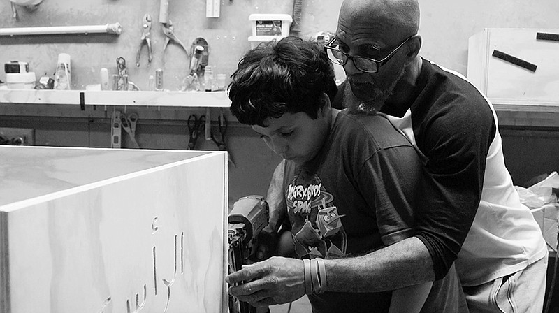 Hanif Muhammad shows Furquan Maynard how to build a casket for the first time.