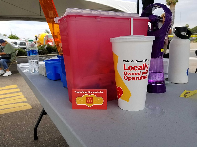 A COVID-19 vaccine setup next to a McDonald's cup that says, 'This McDonald's...