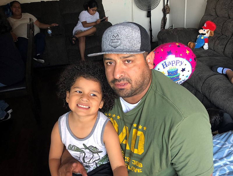 Ramon Toscano poses with his son in his Vista home, June 14, 2021.