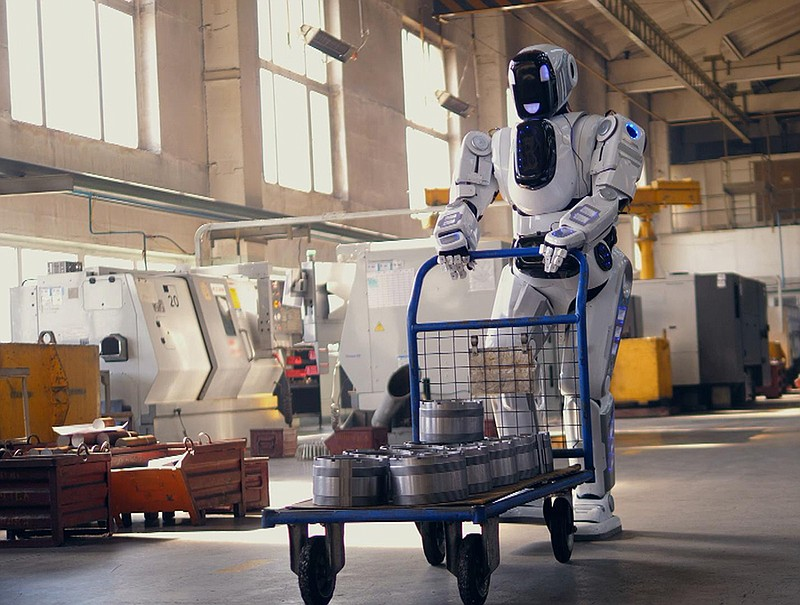 A working robot pulls a cart while walking in a facility.