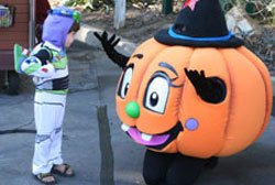 Photo of a child having some fun interacting with a pumpkin character at the Halloween Party and Parade in the San Diego Botanic Garden.
