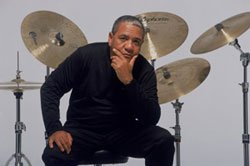 Afro-Cuban jazz drummer Ignacio Berroa sitting in front of his drum set.
