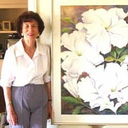 Renowned watercolorist and calligrapher Grace Phillips next to her painting of petunias.