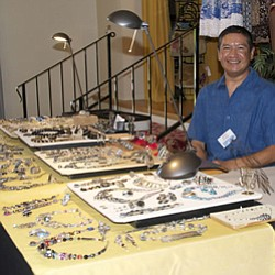 Artist Adrian Arango seated at his display table with jew...