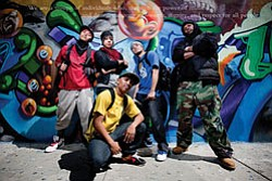 Dancers from Culture Shock pose in front of graffiti art....