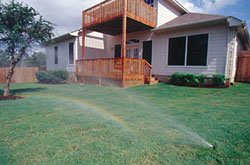 Photo of a house with sprinklers watering the lawn. Image provided courtesy of Rain Bird Corporation.