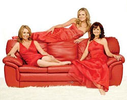 Deirdre Masterson, Wendy Dwyer and Kay Lynch of the Irish Sopranos pose for this photo on a red couch.