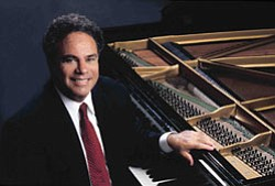 The distinguished American pianist Jeffrey Siegel sitting at the piano