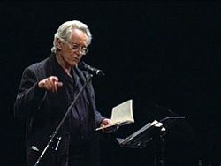 Michael McClure presents on stage.