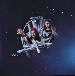 "Promotional graphic titled Ariel Hoops from the Cirque Du Soleil show ""Quidam."" In hoops suspended above the stage, the performers pivot and twirl through the air, at times solo and at times in unison, performing stunning feats of grace and dexterity. Photo credit: Al Seib"