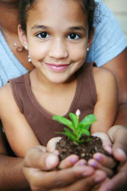 Promotional image of a young child holding a plant in her hands. Credit: The Water Conservation Garden at Cuyamaca College/ shutterstock