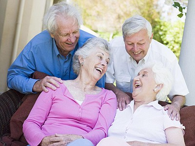 Promotional image of elderly couple laughing on the couch.