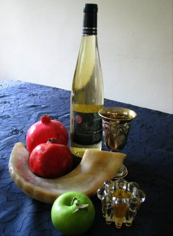 Promotional image of traditional Rosh Hashanah foods: Apples and honey, pomegranates, wine for kiddush.