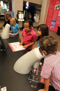 Graphic of children looking into microscopes at a previous DNA Day.