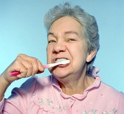 Promotional image of an older adult brushing her teeth.
