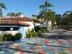 Exterior photo of the Spanish Village Art Center. The charm of an early 20th century village in Spain, complete with colorful flagstone center courtyard and 37 Spanish tile- roofed Art studios. Please stop by and browse our historic village.