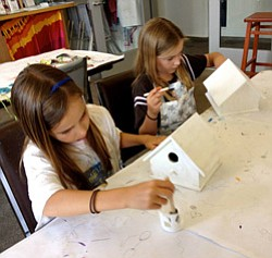 Promotional image of two young girls participating in Bravo School of Art's Birdhouse workshop. Courtesy image of Bravo School of Art.