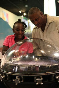 Promotional image of father and daughter discovering the wonders of science at the Reuben H Fleet Science Center.