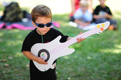 Image of a young boy playing a guitar at a previous Hullabaloo Family Arts Festival.