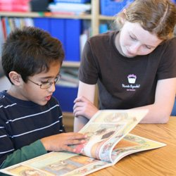 Promotional image of two children looking at a book at The Gillispie School. Courtesy image of The Gillispie School.