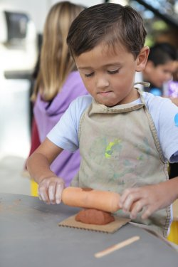 Image of a boy rolling clay at the New Children's Museum.