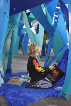 Child reading inside Three-Horned Beast and Baby Beast by Layer in TRASH at NCM.  Courtesy image of New Children's Museum.