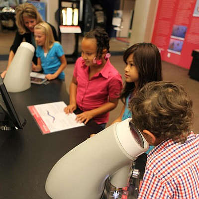 Promotional photo of young visitors at a microscope table in the Ruben H. Fleet Science Center. Courtesy of Ruben H. Fleet Science Center