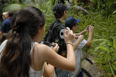 Image of children taking photos in Balboa Park during the Photojournalism For Beginners summer camp at the MOPA.