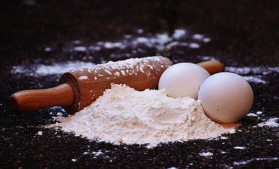 Photo of a rolling pin next to flour and eggs.