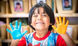 Photo of a child smiling with paint on his hands. Courtesy of the Child Devel...
