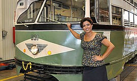 Photo of Elsa Sevilla standing next to the SDMTS Vintage Trolley. Courtesy of...