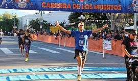 A Carrera de los Muertos runner crosses the finish line. This year's Day of t...