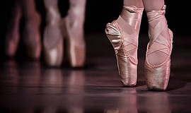 Photo of ballet dancers standing on their toes.
