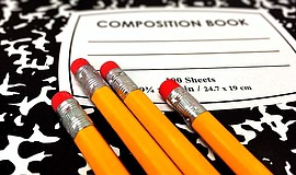 Photo of a composition book and pencils. Courtesy of Pixabay.