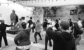Photo of a group practicing Tai Chi at the SDCHM Chuang Garden.