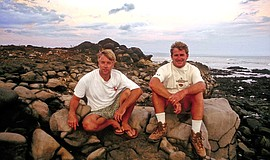 Craig Peterson and Kevin Naughton sitting on rocks at a beach.