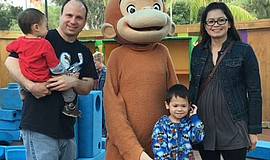 A family poses for a photo with Curious George at  San Diego Children's Disco...