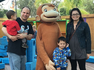 A family poses for a photo with Curious George at  San Diego Children's Discovery Museum