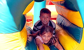Promotional photo of kids trying out an inflatable ride at National City Pump...