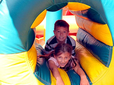Promotional photo of kids trying out an inflatable ride a...