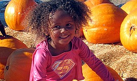 Promotional photo of young girl with pumpkins at Del Mar Pumpkin Station.