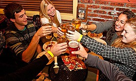Promotional photo of people enjoying pizza and beer. Courtesy of Woodstock's ...