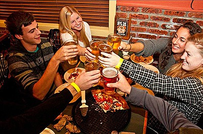 Promotional photo of people enjoying pizza and beer. Cour...